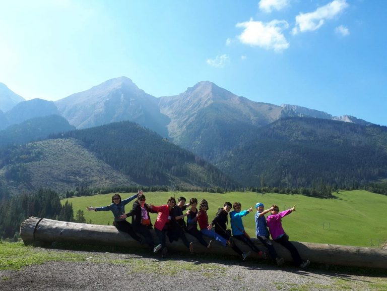 Happy hikers sitting on a log with Tatra mountains in the background
