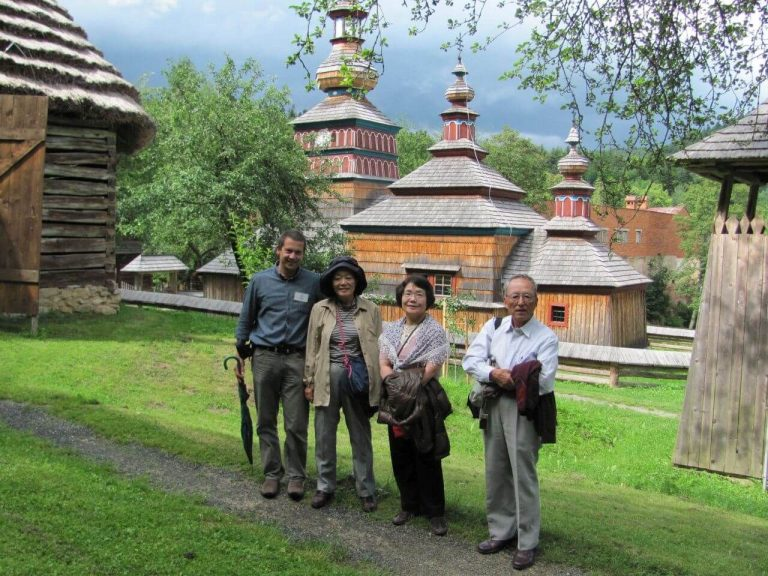 Small private tour group in front of the wooden church in Bardejov Spa