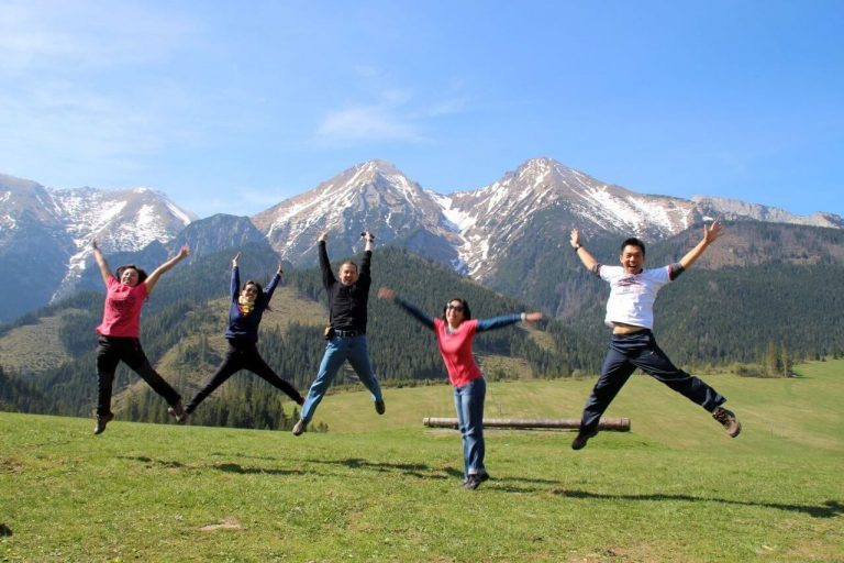 Happy travellers jumping up with Tatra mountains in the background